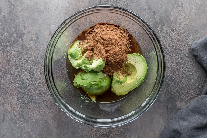 Avocados and other chocolate filling ingredients in a glass bowl.
