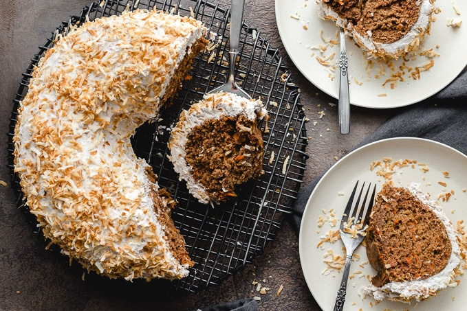 Carrot bundt cake being sliced into pieces and placed on small plates.