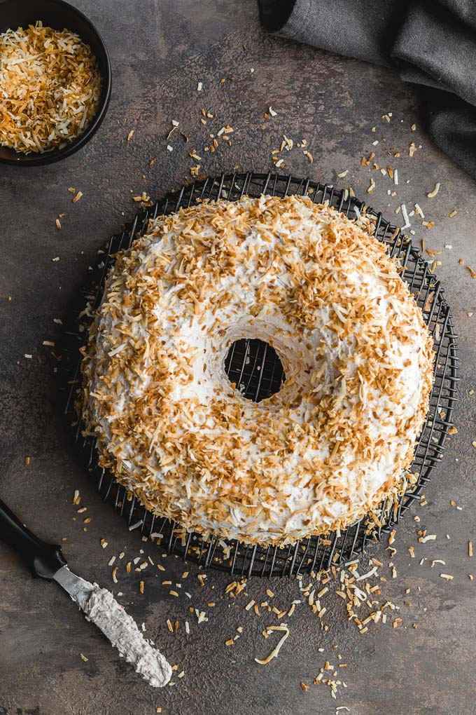 Coconut carrot bundt cake frosted with coconut whip and covered in toasted coconut.