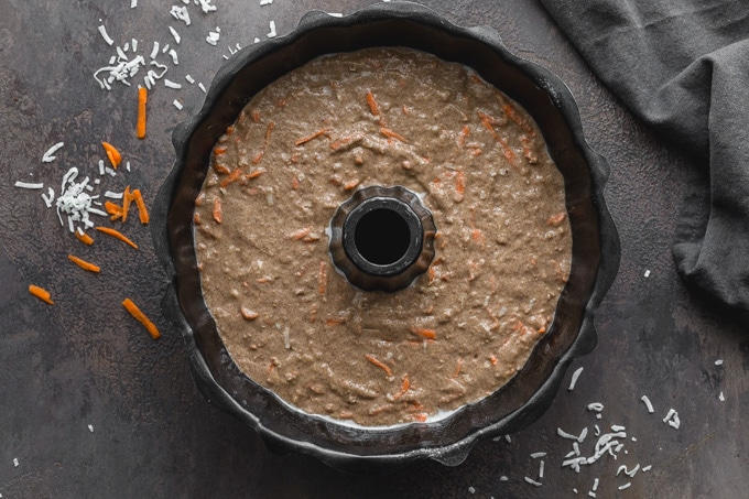 Egg-free carrot cake batter poured into a greased bundt pan.