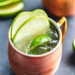 Green Apple Irish Mule in a copper mug and garnished with apple slices and lime wedges.