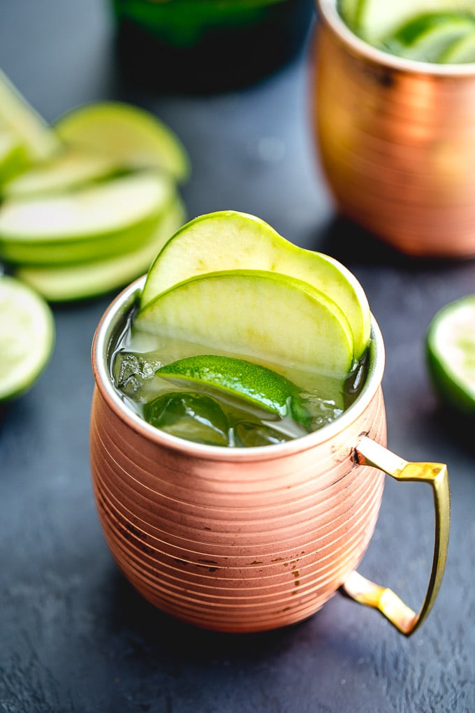 Green apple whiskey mule in a copper mug and garnished with apple slices.