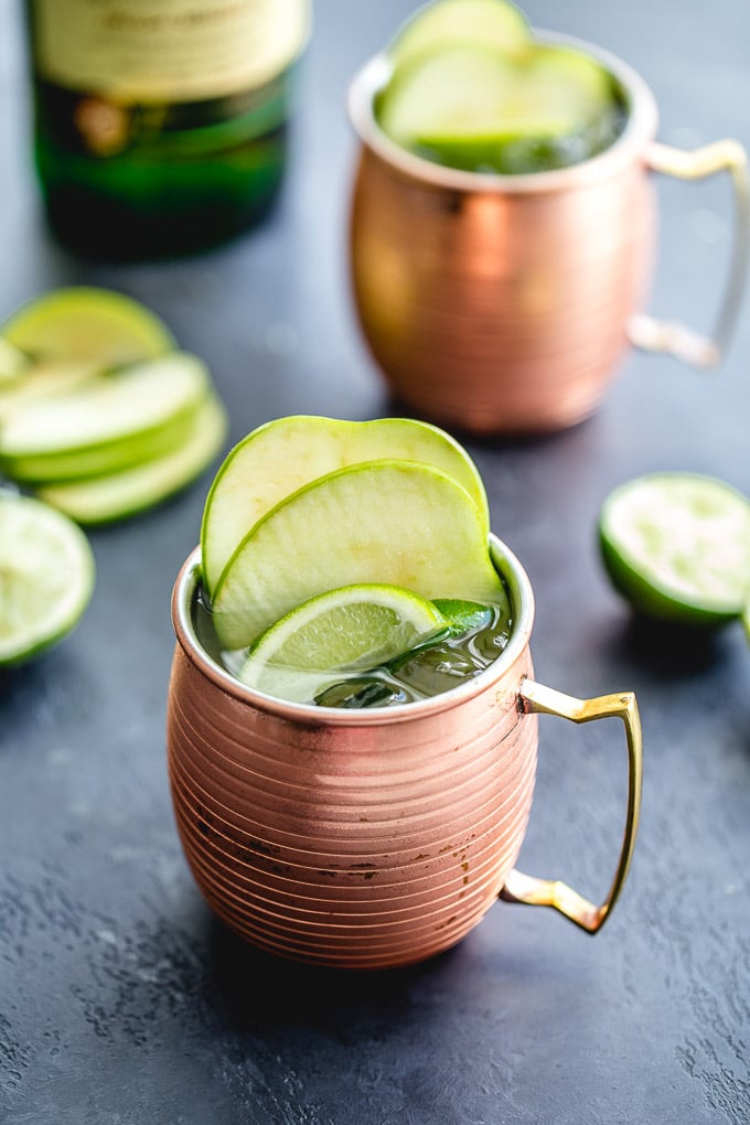 Irish mules in copper mugs with a bottle of whiskey in the background.