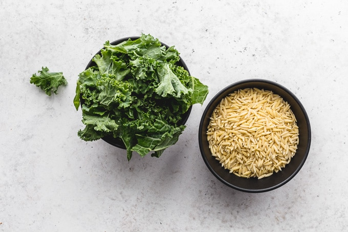 Small bowls of kale and orzo on a light coloured surface.