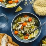 Instant Pot Chicken Orzo Soup served up in blue bowls and garnished with lemon slices.