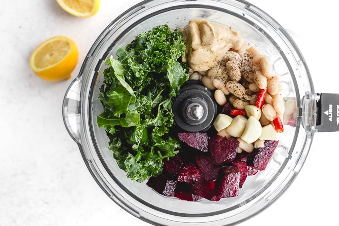 Overhead view of ingredients to make beet hummus in a food processor bowl.