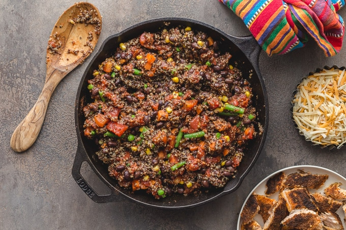 Cooked quinoa, veggies and beans mixed together in a skillet.