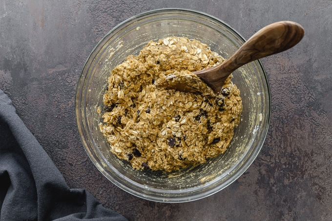 Oatmeal cookie dough in a glass bowl with a wooden spoon.