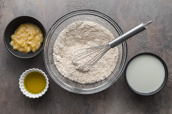 Dry ingredients being whisked together in a glass bowl.