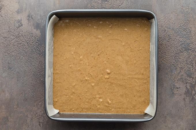 Banana cake batter poured into a square pan.