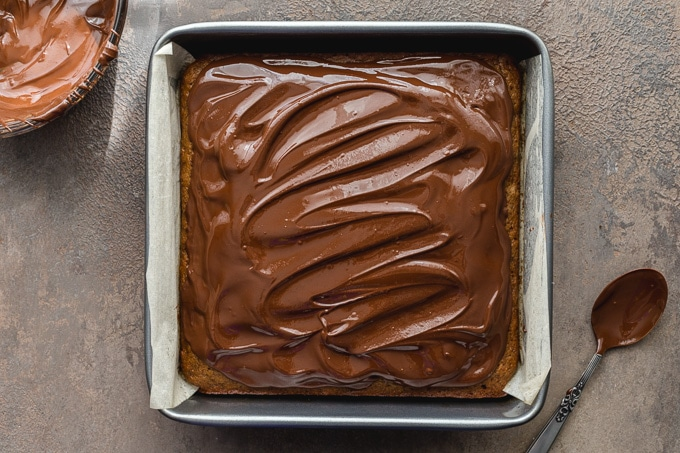 Cake topped with melted chocolate and almond butter.
