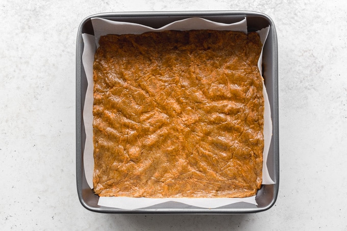 Carrot cake cookie dough pressed into a square pan.