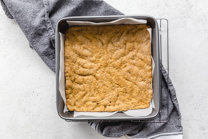 Carrot cake cookie layer baked up in a square pan.