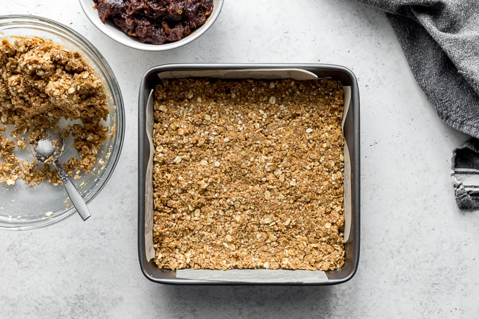 Crumble mixture pressed into the bottom of a square metal pan lined with parchment paper.