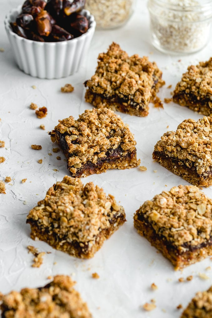 Healthy date squares on a sheet of wax paper with dates in the background.