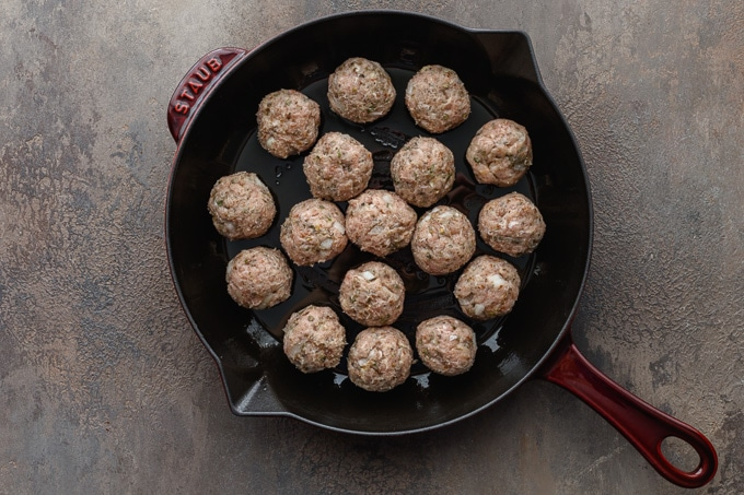 Uncooked turkey meatballs arranged in a cast iron skillet.