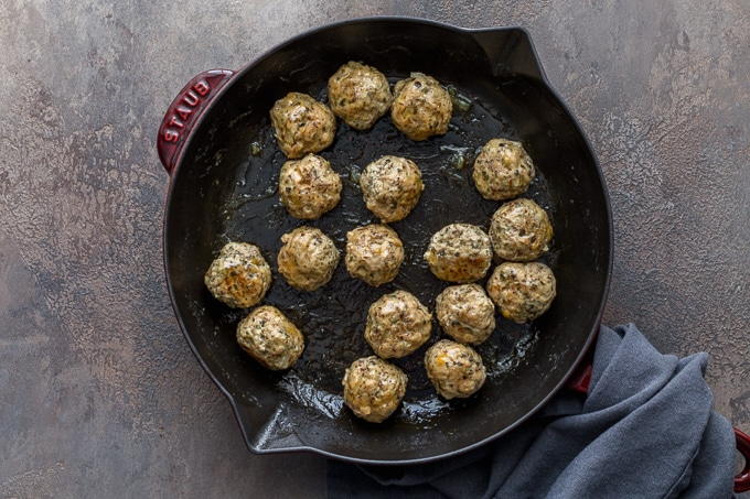 Overhead view of cooked meatballs in a skillet.