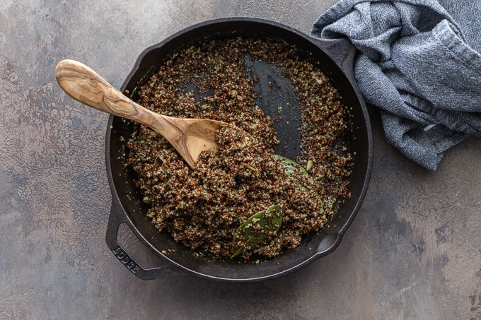 Cooked quinoa in a black cast iron skillet.
