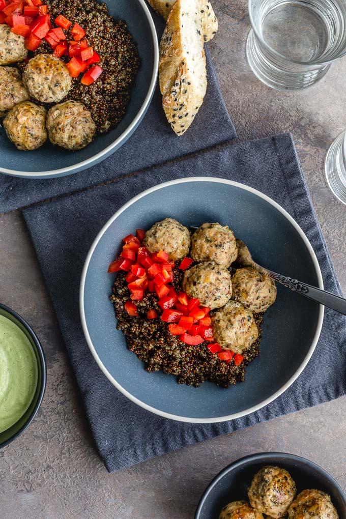 Turkey meatballs with quinoa in blue bowls on dark grey napkins.