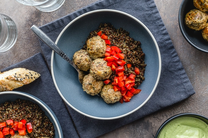 Overhead view of turkey meatballs, quinoa and peppers in a blue bowl.
