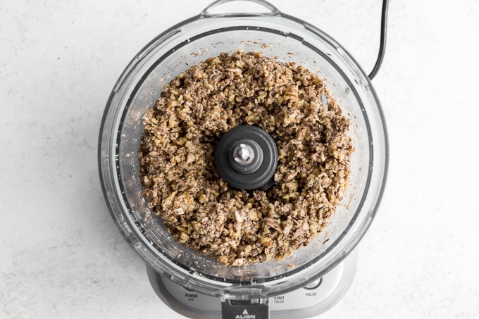 Walnut and mushroom crumble mixture in a food processor bowl.