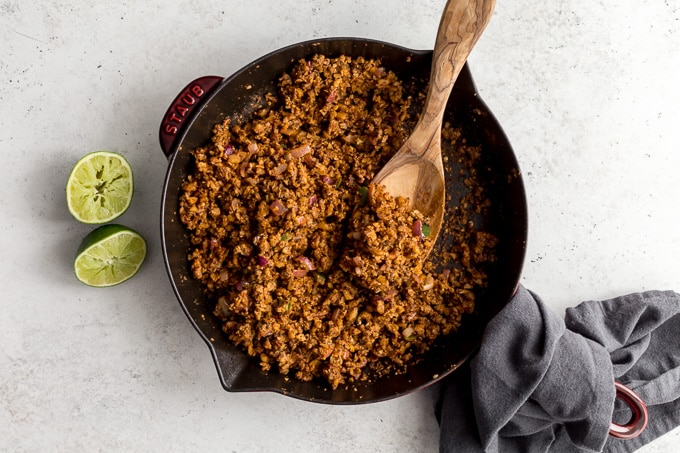 Vegan taco meat prepared in a skillet with a wooden spoon inserted into it.