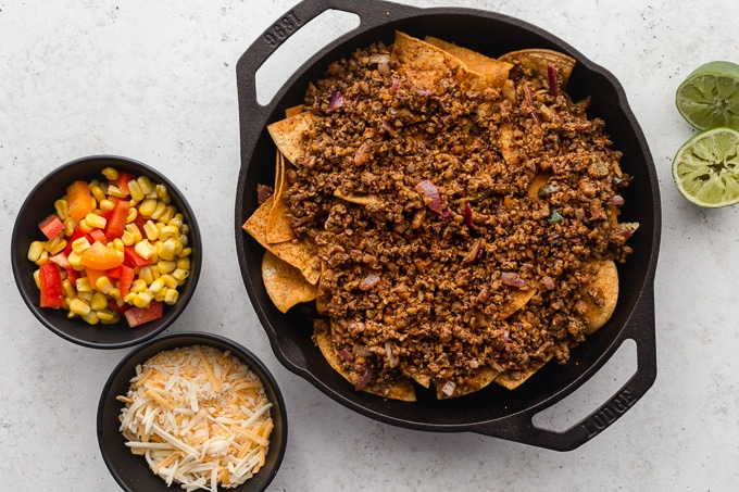 Meatless nachos being assembled in a skillet.
