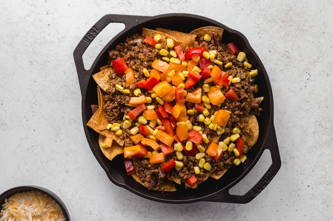 Meatless nachos with chopped veggies arranged on top.