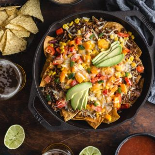 Loaded Veggie Nachos in a cast iron pan surrounded by dips, chips and beer.
