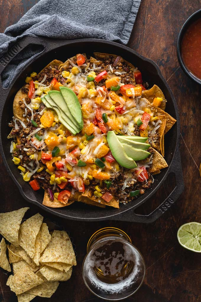 Overhead view of loaded veggie nachos with chips and beer on the side.