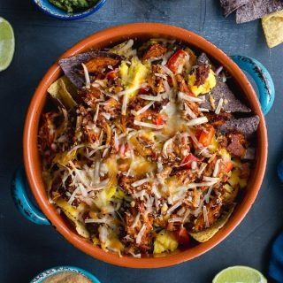 Pulled pork breakfast nachos prepared in a round orange dish with queso, salsa and guacamole.