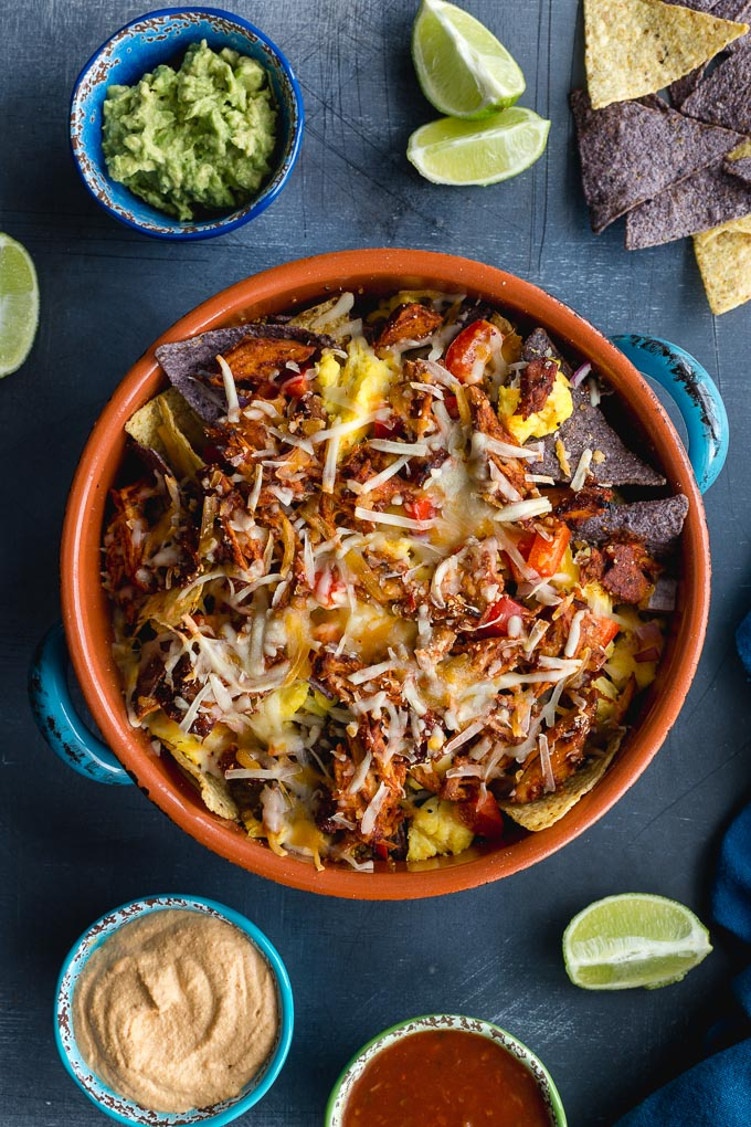 Breakfast nachos baked in a casserole dish with guacamole, queso and salsa off to the side.