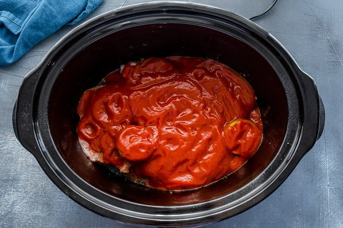 Pork chops covered in tomato sauce in a slow cooker.