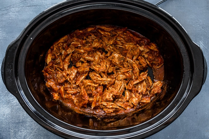 Cooked pulled pork in a slow cooker.