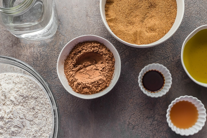 Ingredients to make a chocolate cake arranged in individual dishes.