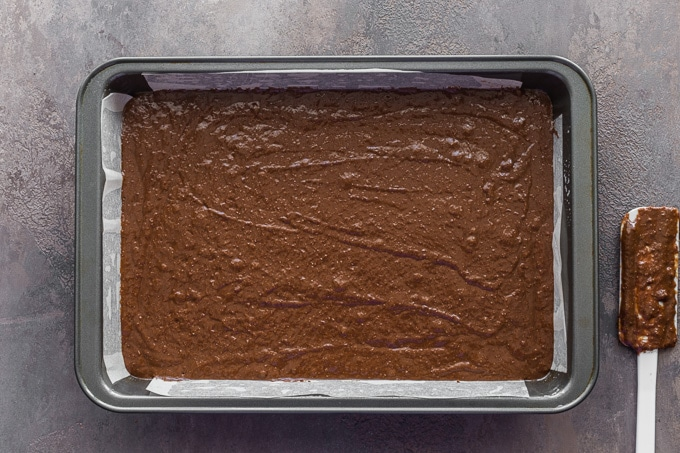 Chocolate cake batter spread out in a 9x13 pan.