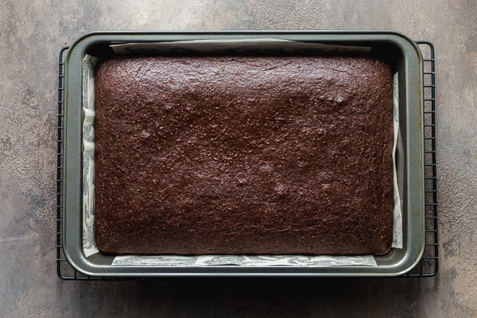 Chocolate sheet cake cooling in a pan on a wire rack.