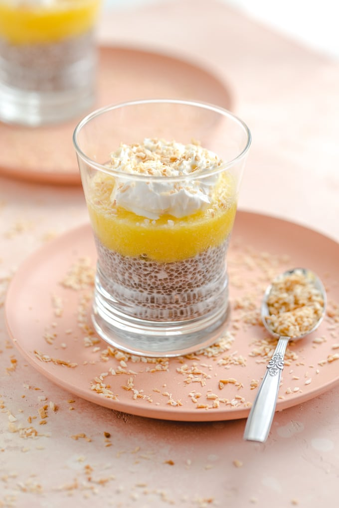 Side view of a glass of pineapple coconut chia pudding on a pink plate.