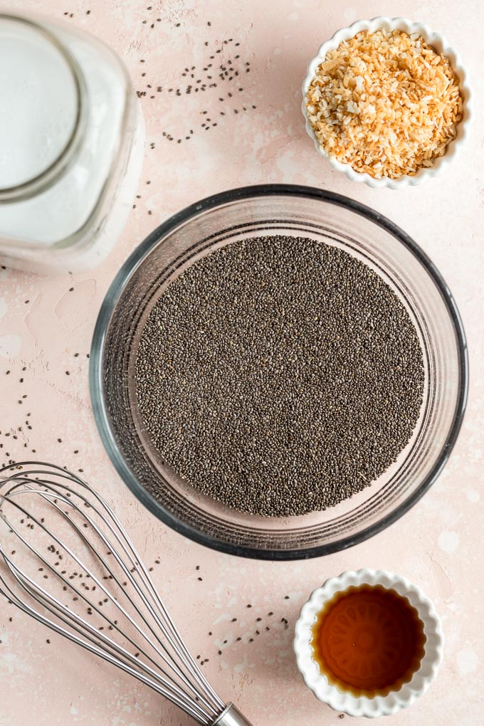 Ingredients to make coconut chia pudding arranged on a pink surface.