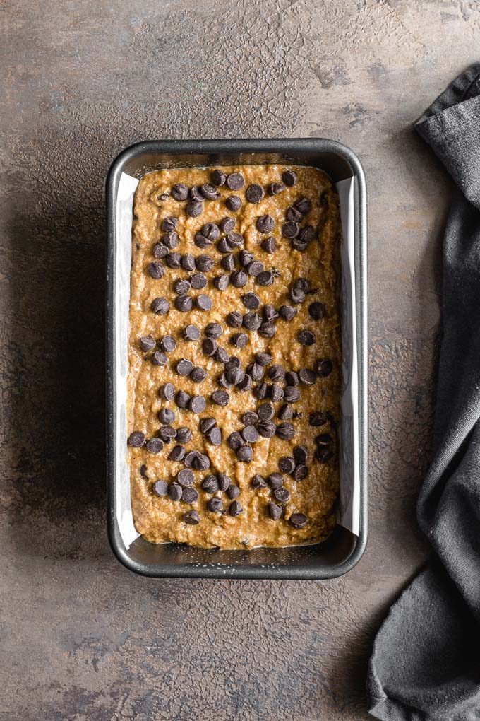 Banana bread batter in a loaf pan and topped with chocolate chips.