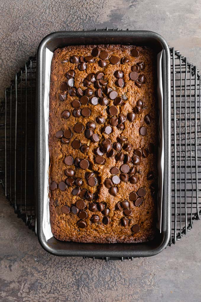 Chocolate chip banana bread baked up in a loaf pan and cooling on a wire rack.