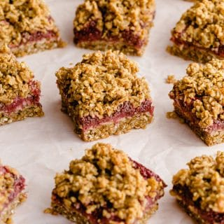 Strawberry oat bars arranged on parchment paper on a pink surface.
