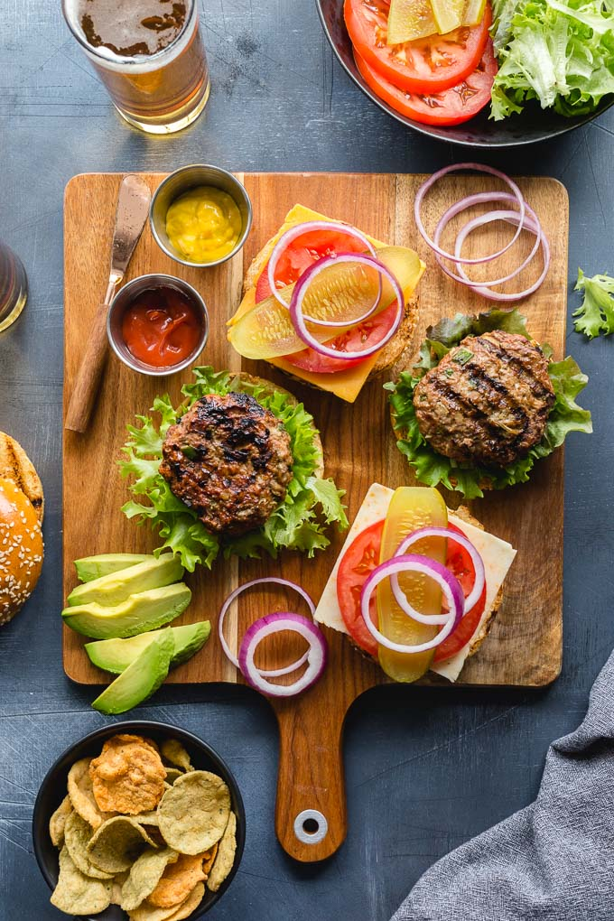 Overhead view of burgers and burger toppings arranged on a wooden board.