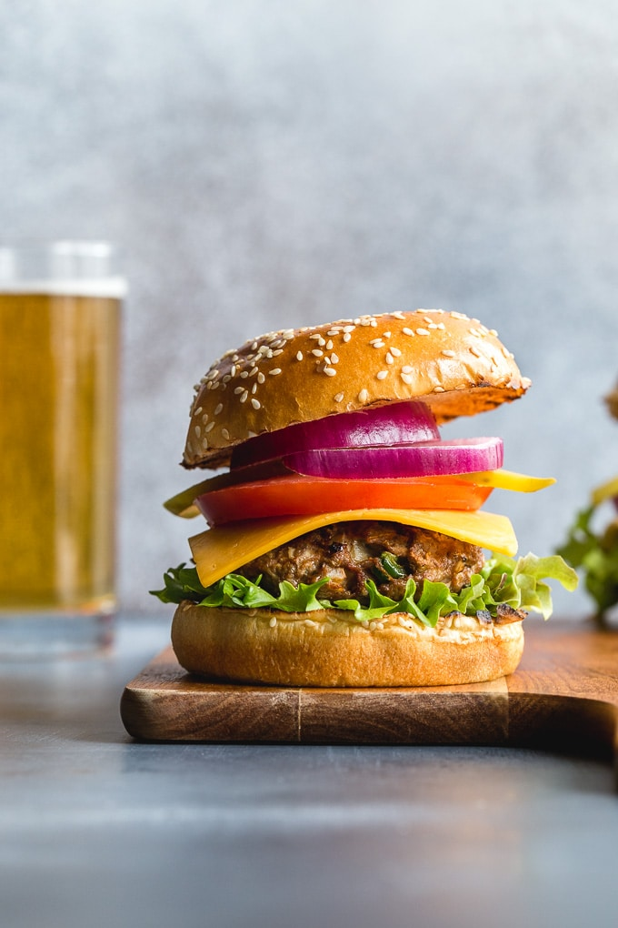Side view of a turkey jalapeno burger on a wooden board with a glass of beer in the background.