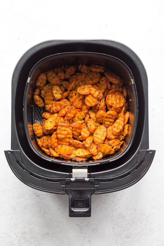 Overhead view of air fried carrots in an air fryer basket.