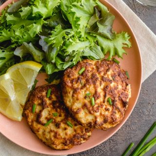 Air Fryer Salmon Patties on a pink plate with some fresh greens.