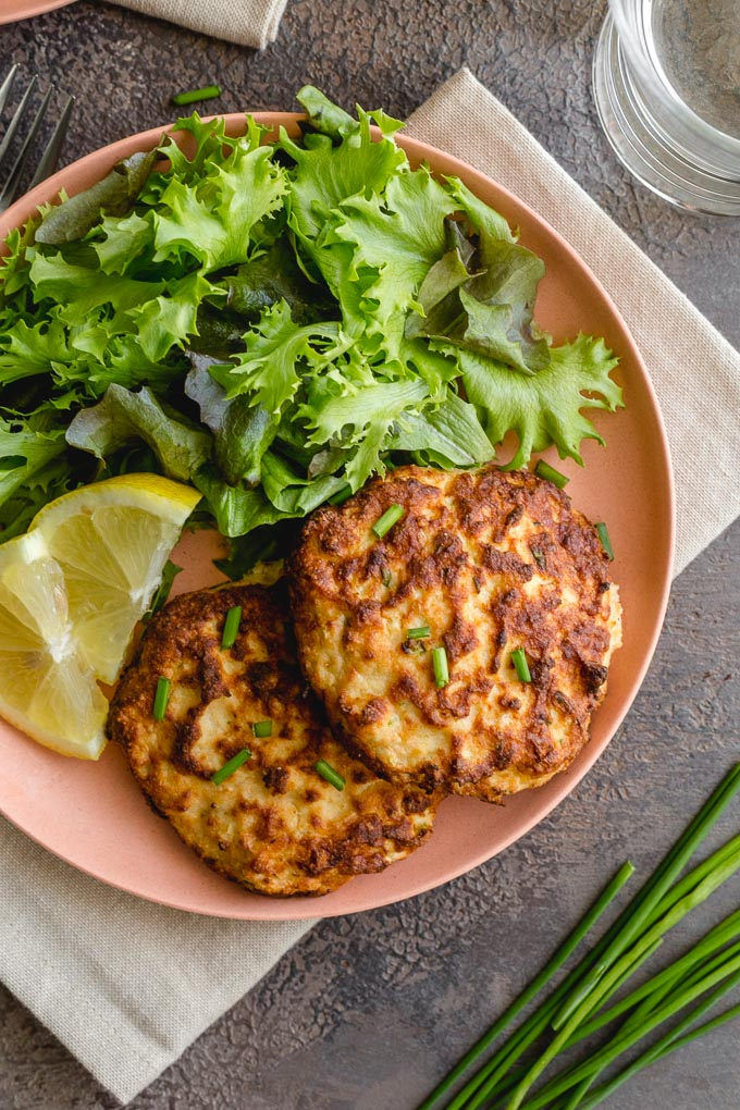 Salmon patties with fresh salmon served with greens and lemon slices.