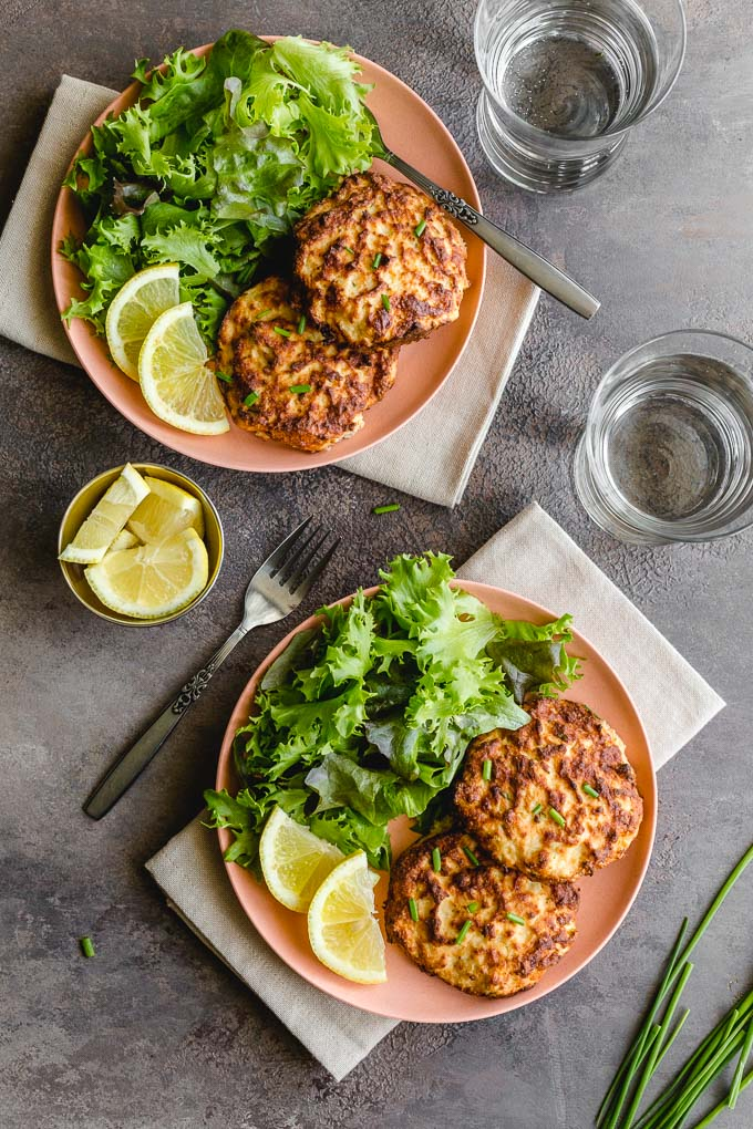 Overhead view of two plates with salmon patties and greens and glasses of water off to the side.
