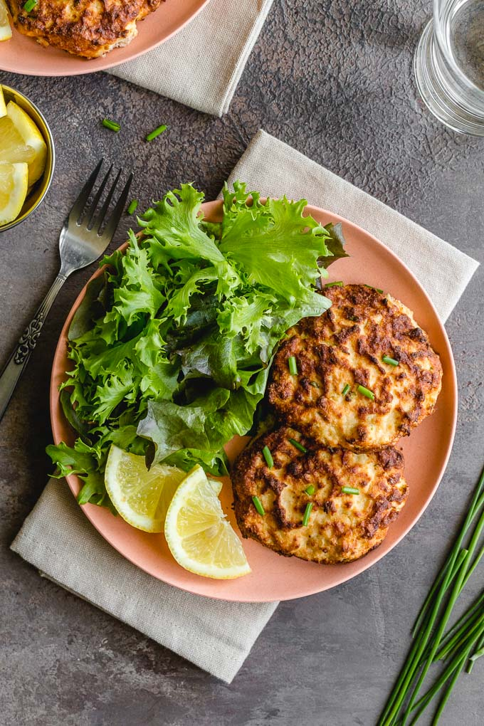 Two air fryer salmon cakes on a pink plate with leafy greens and lemon slices.