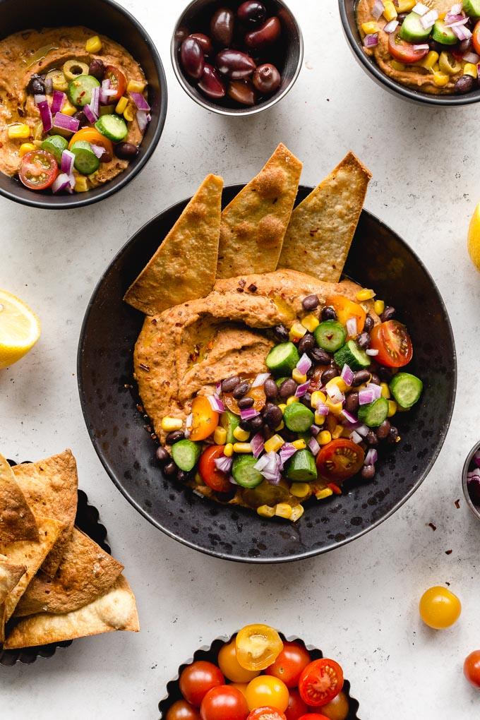 Black bean hummus bowls loaded with veggies and tortilla chips.